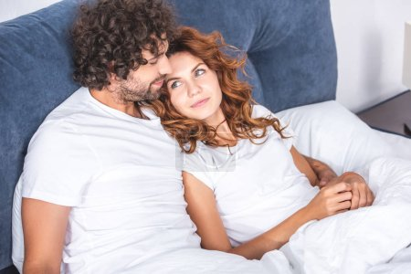 Photo for High angle view of beautiful happy young couple lying together on bed - Royalty Free Image