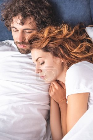 top view of beautiful young couple sleeping together in bed