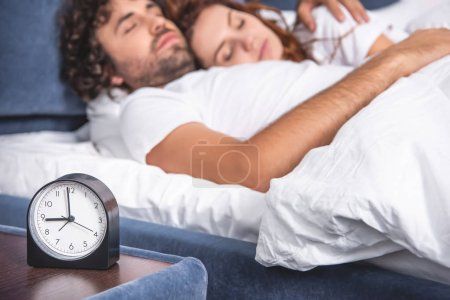 close-up view of alarm clock and young couple sleeping together behind
