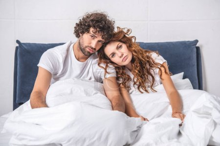 Photo for Young couple suffering from headache, sitting on bed and looking at camera - Royalty Free Image