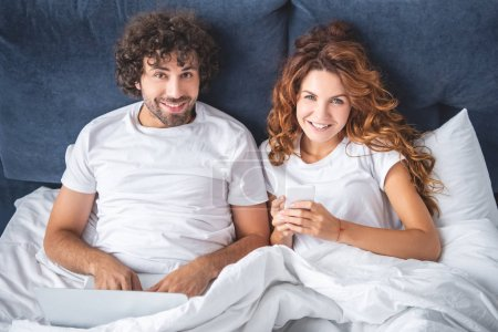 Photo for High angle view of happy young couple using digital devices and smiling at camera while lying in bed - Royalty Free Image