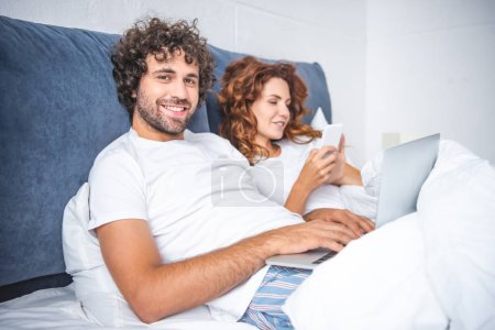 Photo for Happy young couple using digital devices in bed - Royalty Free Image