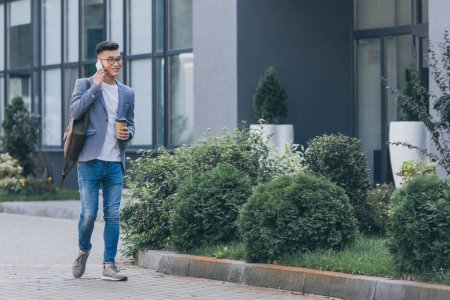 stylish asian man with coffee to go talking on smartphone while walking on street