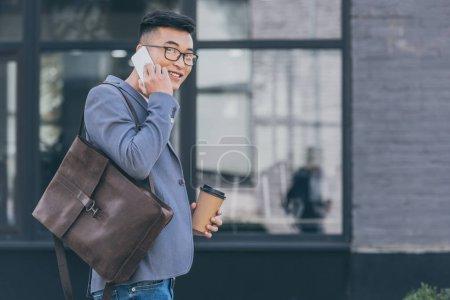 Foto de Guapo hombre asiático con mochila de cuero y café para ir hablando por teléfono inteligente - Imagen libre de derechos