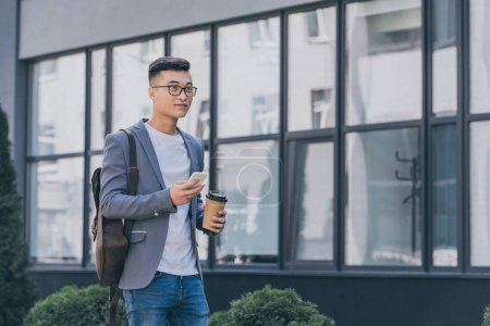 asian man in gray jacket with coffee to go using smartphone on street