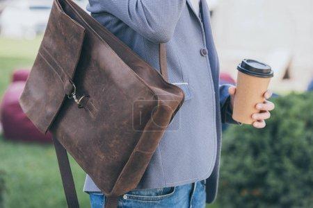 Photo pour Vue recadrée de l'homme avec sac à dos en cuir tenant tasse jetable de café - image libre de droit