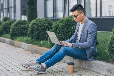confident asian freelancer working on laptop while sitting on sidewalk with disposable cup of coffee