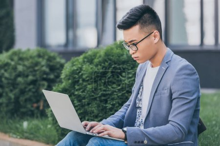 confident asian freelancer in eyeglasses working on laptop while sitting on sidewalk