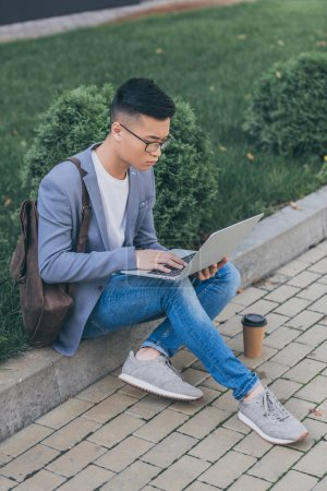 handsome asian man teleworking with laptop while sitting on sidewalk