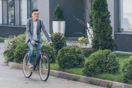 stylish smiling asian man cycling on bicycle in city
