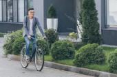 """Постер, картина, фотообои """"стильный, улыбаясь азиатских человек Велоспорт на велосипедов в городе"""""""