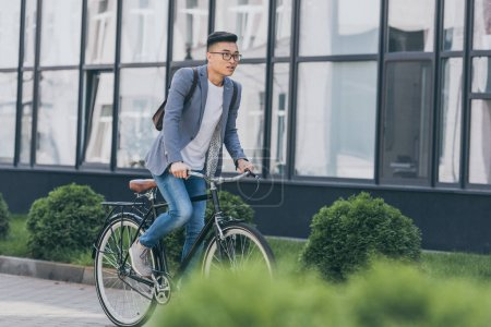 Photo for Stylish asian man in gray jacket biking in city - Royalty Free Image