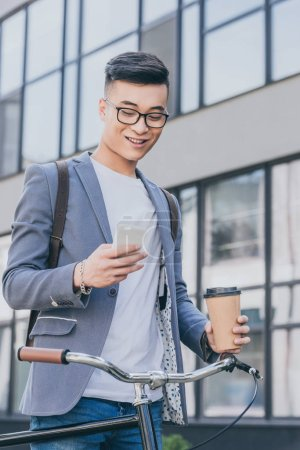 Photo for Happy asian man with coffee to go looking at smartphone and standing near bike - Royalty Free Image