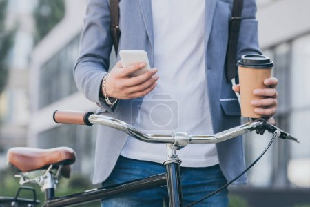 partial view of man holding disposable cup of coffee and using smartphone near bicycle
