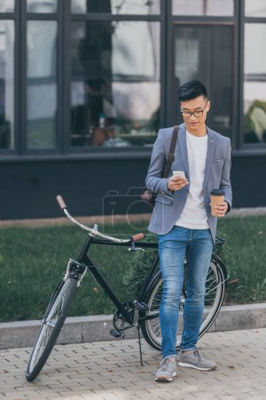 stylish asian man with disposable cup using smartphone and standing near bicycle