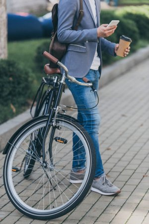 Photo for Cropped view of man with coffee to go using smartphone and leaning on bicycle - Royalty Free Image