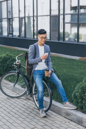 Photo for Smiling asian man with paper cup using smartphone and sitting on bicycle - Royalty Free Image
