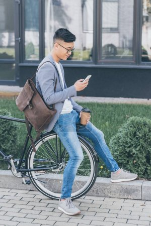 handsome asian man with leather backpack and coffee to go using smartphone and sitting on bike