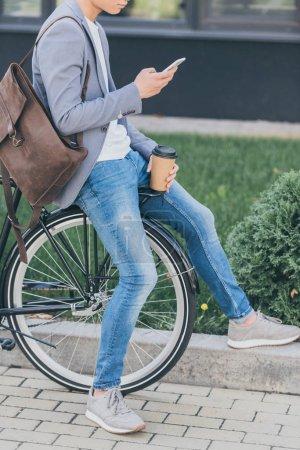 Photo pour Vue recadrée de l'homme avec café pour aller à l'aide d'un smartphone et assis sur le vélo - image libre de droit