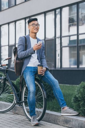 happy asian man with disposable cup of coffee using smartphone and sitting on bicycle