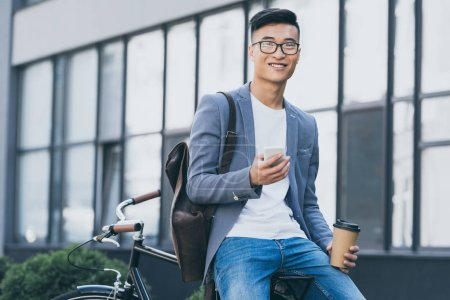 Photo for Smiling asian man with coffee to go using smartphone and sitting on bicycle - Royalty Free Image