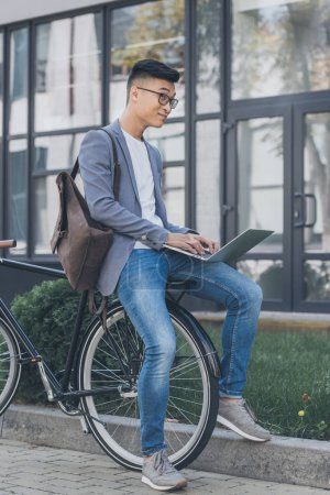 pensive asian teleworker with leather backpack using laptop while sitting on bicycle