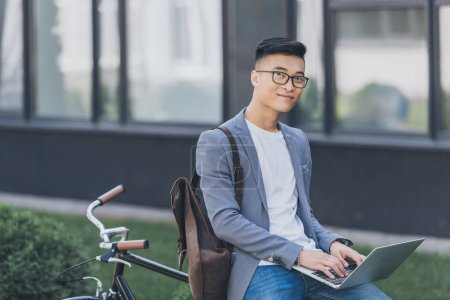 Photo for Smiling asian teleworker using laptop while sitting on bicycle - Royalty Free Image