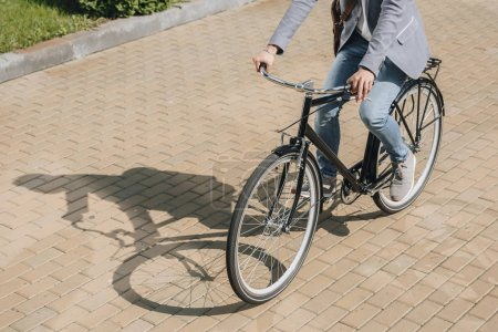 Photo for Cropped view of stylish man cycling on bicycle in city - Royalty Free Image