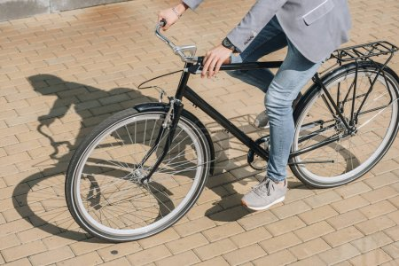 cropped view of young stylish man riding bicycle in city