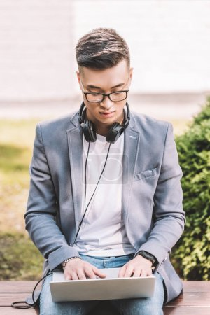 confident asian freelancer working on laptop on bench
