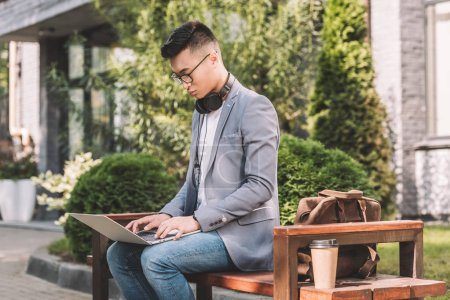 asian teleworker using laptop while sitting on bench with leather bag and coffee to go