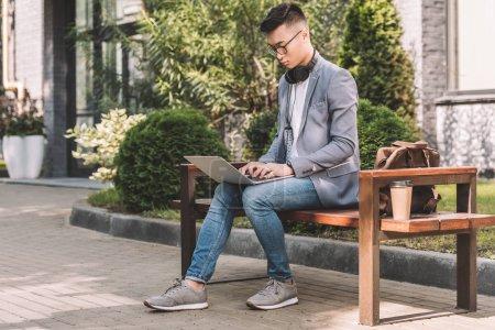 Foto de Seguro freelancer asiático trabajando en ordenador portátil sentado en Banco con bolso de cuero café para ir - Imagen libre de derechos