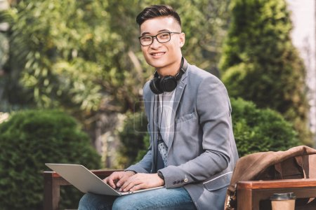 Photo for Smiling asian freelancer working on laptop while sitting on bench - Royalty Free Image