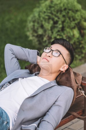 handsome thoughtful asian man in eyeglasses dreaming and lying on bench