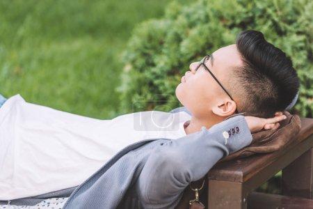 stylish asian man in eyeglasses sleeping on bench