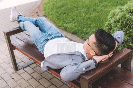 stylish man in gray jacket resting on bench