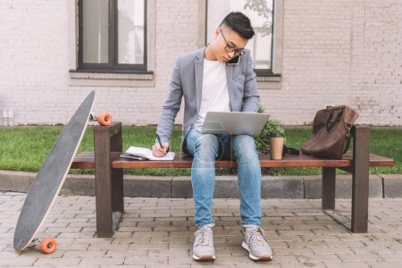 confident asian teleworker writing in planner while talking on smartphone and using laptop on bench with longboard