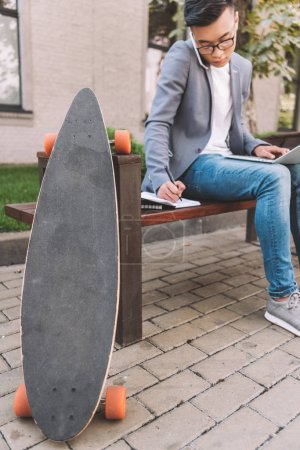 asian teleworker writing in planner while using smartphone and laptop on bench with longboard