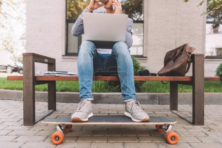 cropped view of freelancer working with laptop and smartphone while sitting on bench with longboard