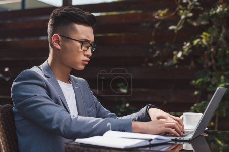 side view of concentrated asian businessman remote working on laptop in cafe