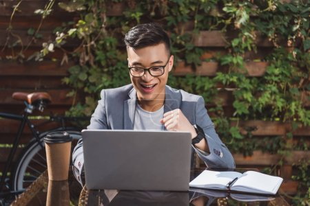 happy asian businessman looking at laptop screen at tabletop with coffee to go