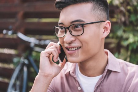 Photo for Smiling asian man in eyeglasses talking on smartphone - Royalty Free Image
