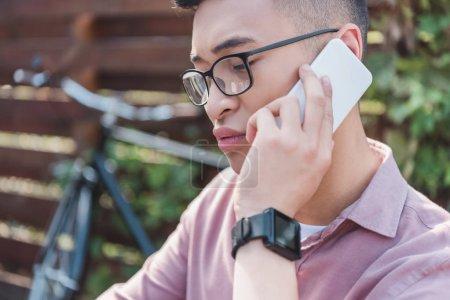 focused asian man in eyeglasses talking on smartphone