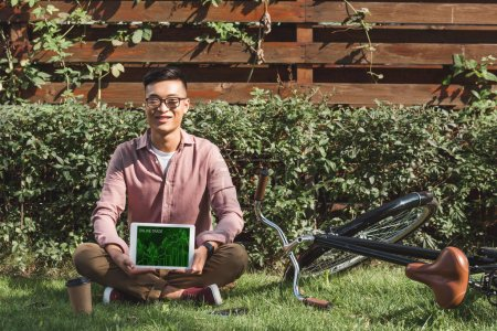 smiling asian man sitting on green grass and showing tablet with online trade inscription on screen in hands in park