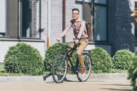 asian young man with backpack riding bicycle on street