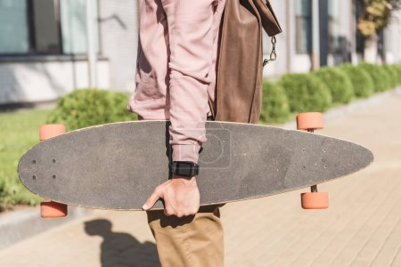 Photo for Partial view of man with backpack holding longboard on street - Royalty Free Image