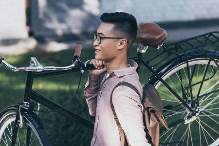 Photo pour Asiatique homme transportant des vélos pendant qu'il marchait sur la rue souriant - image libre de droit