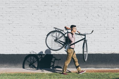 side view of asian man carrying bicycle while walking on street