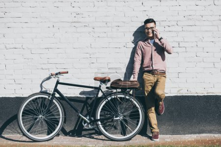 smiling asian man in stylish clothing talking on smartphone at bicycle on street