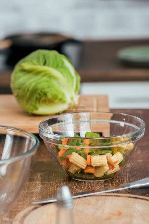 légumes pour la salade dans un bol, chou sur planche à découper sur le dessus de la table dans la cuisine